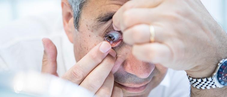 Man inserting contact lenses