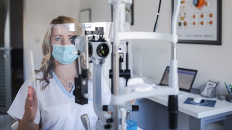 Ophthalmologist sitting by phoropter and wearing protective mask