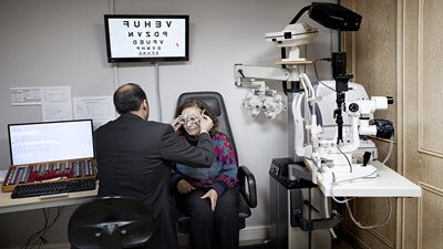 A male optometrist looking at a female patients eyes