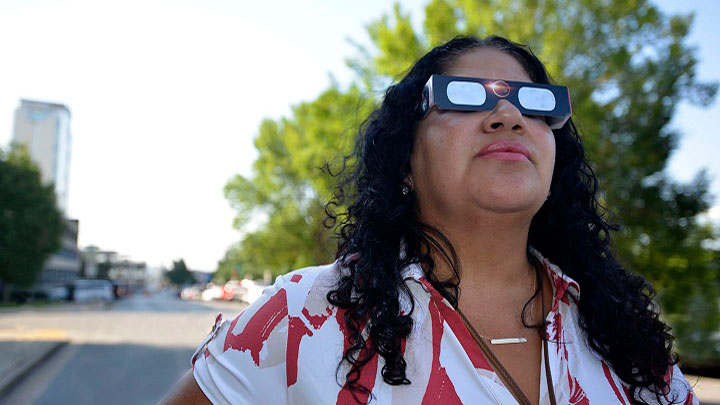 Woman in solar eclipse protecting sunglasses