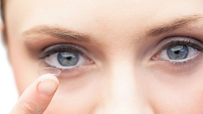 Women holding a contact lens