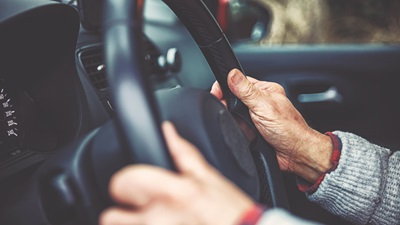 old persons hands on wheel