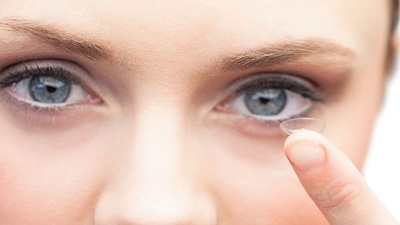Woman with contact lens on finger