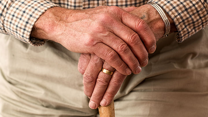 Elderly man clasping his hands together