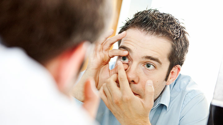 A man putting a contact lens in