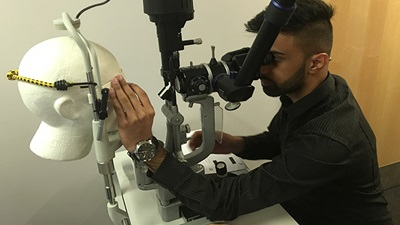 Optometrist at EOS workshop practising clinical skill on model head