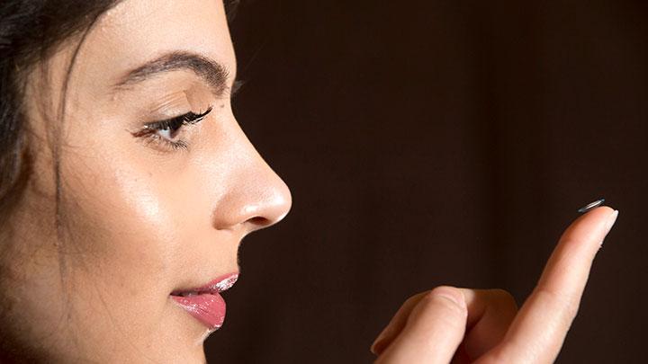 Women holding a contact lens