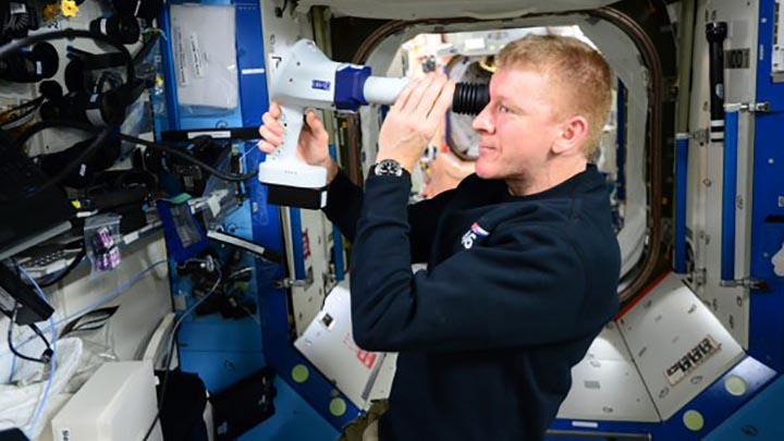Astronaut Tim Peake using a fundoscope on the ISS