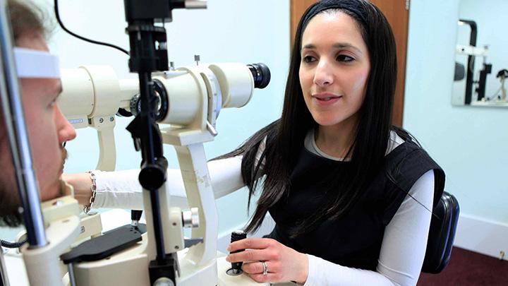 Optometrist giving sight test