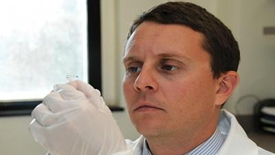 Man looking at contact lens