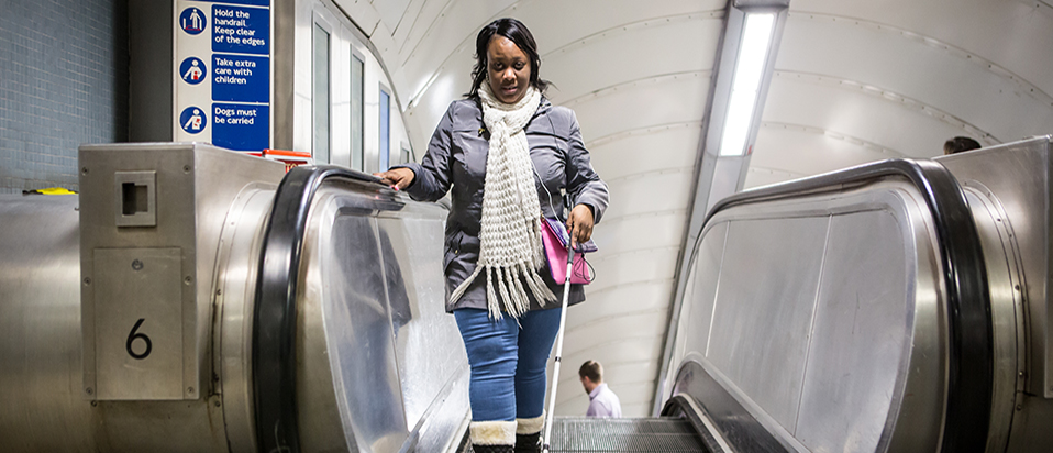 Visually impaired lady on tube esculator