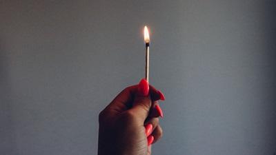 Hand holding matchstick
