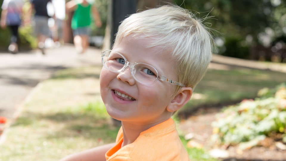 Little boy wearing glasses with dinosaur frames