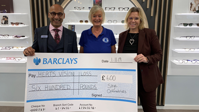 Skye optometrists holding cheque
