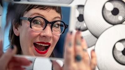 A lady trying on eyewear at Opti