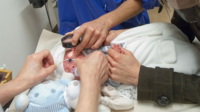 A baby having its eye examined