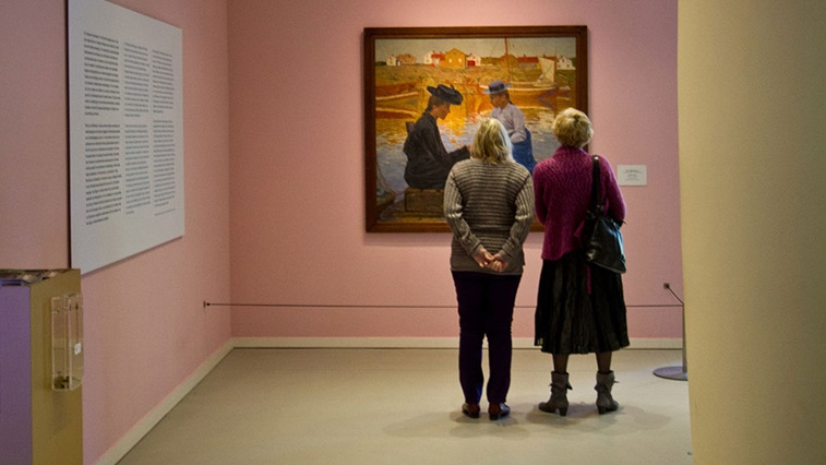 Two women looking at art work