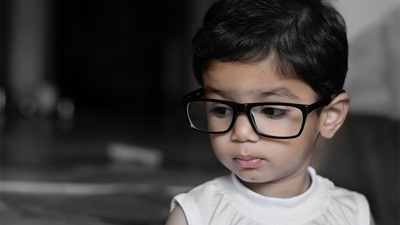 A young child wearing spectacles