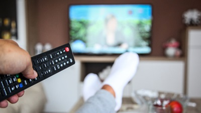 person holding tv remote