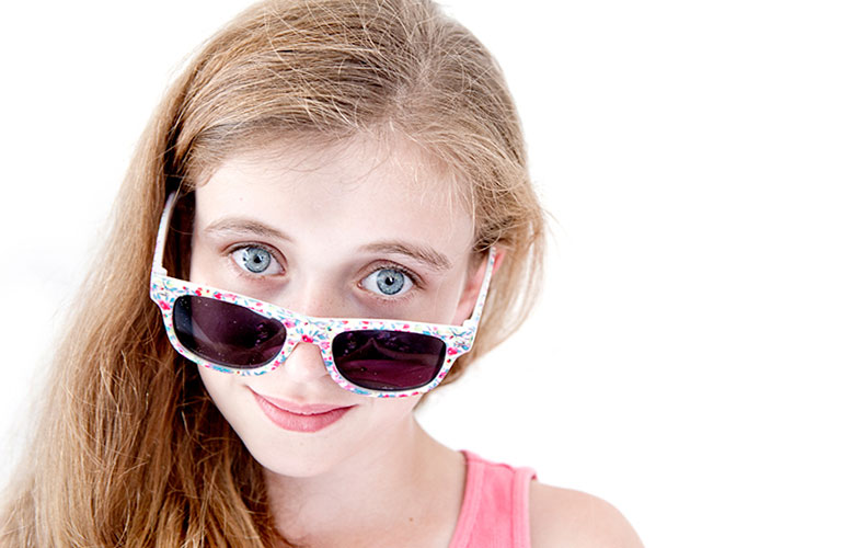 young girl peering over sunglasses